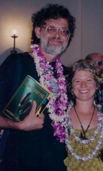 Terence McKenna and girlfriend Christy Silness at the 1999 AllChemical Arts Conference. Terence is holding the copy of 'Land Without Evil' that Matt Pallamary sent to be gifted to him at the conference, which was the last place most people saw Terence before his death.